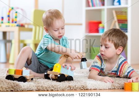 Children playing with wooden car at home or daycare.  Educational toys for preschool and kindergarte