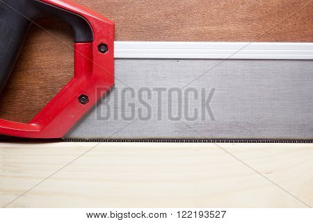 Toothed steel hand saw cutting through a new boards of wood surrounded by wood chips with nobody in the frame in a DIY carpentry woodworking or joinery concept