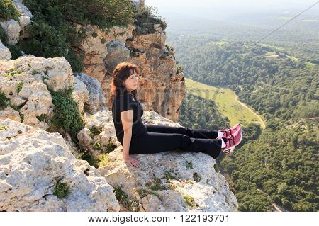woman in a black tracksuit sitting on the cliff and looking into the distance