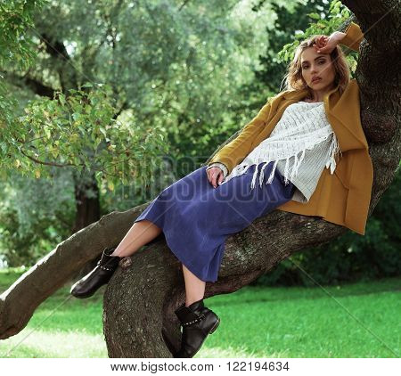 Young beautiful woman posing on a tree. Glamour fashion portrait. Autumn park.