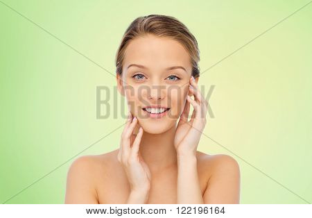 beauty, people and health concept - smiling young woman with bare shoulders touching her face over green natural background