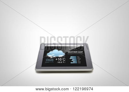 electronics, technology, weather cast and modern gadget concept - close up of tablet pc computer with meteo forecast over gray background