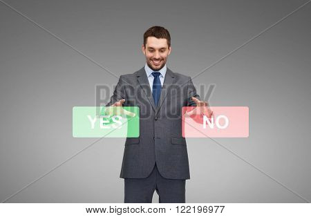 business, technology, choice and people concept - smiling businessman with yes and no buttons