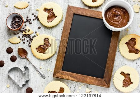 Recipe traditional Easter biscuits shaped bunny. Beautiful composition of food easter dessert chocolate cookies ingredient blank space for text on chalkboard in wooden frame top view