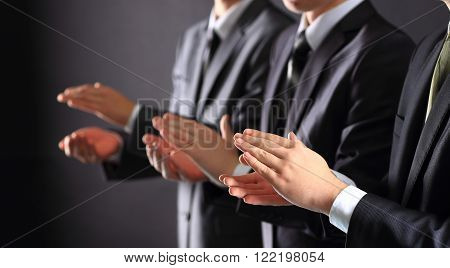 business team applauding against a black background