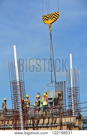 SELANGOR, MALAYSIA -NOVEMBER 21, 2015: A group of construction workers pouring concrete using concrete bucket into the beam form work at the construction site.