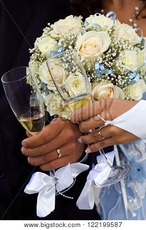 glasses of champagne and a bouquet of flowers in the hands of the bride and groom