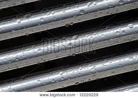 Rain drops cling to stainless steel tubes