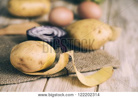 closeup of some potatoes, a half raw red onion and some brown chicken eggs, to prepare a spanish omelet or some other recipe, on a rustic wooden table