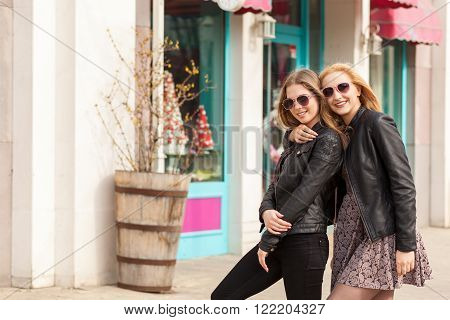 Two Smiling Girls In Sunglasses Embracing And Looking At Camera