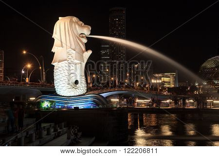 Singapore, Singapore - May 18, 2015: The Merlion statue in Singapore at night. The Merlion is a traditional creature in Singapore with a lions head and a body of fish.