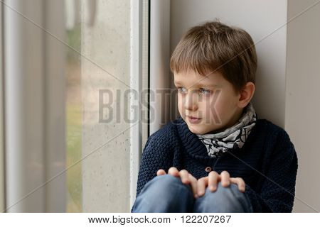 Thoughtful little boy sitting on the windowsill and looking through the window. Rainy day ** Note: Shallow depth of field