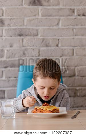 7 years old boy eating lasagne in dining room.