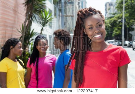 African woman with dreadlocks and girlfriends in the city