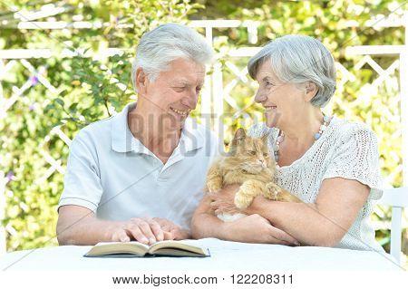 Happy senior couple on the veranda with cat.