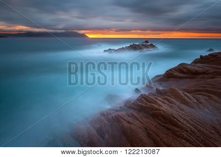 Beautiful dawn on Greek coast of Aegean sea with holy mountain Athos in background. Long exposure shot with motion blur effect. Chalkidiki Greece.