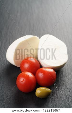 sliced mozarella ball with tomato and olives on slate background, shallow focus