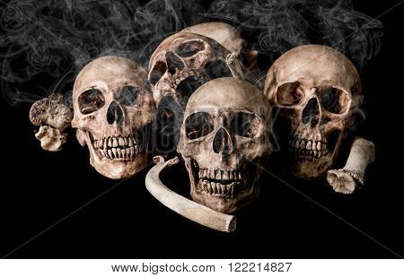 Still life human skull and bones on smoky, genocides concept and horror darkness