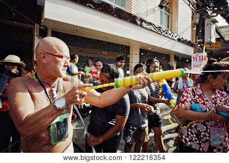 KO SAMUI THAILAND - APRIL 13: Unidentified man shooting water at other people in a water fight festival or Songkran Festival (Thai New Year) on April 13 2014 in Chaweng Main Road Ko Samui island Thailand.