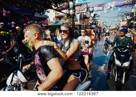 KO SAMUI, THAILAND - APRIL 13: Unidentified wet happy tourists on a bike on Songkran Festival (Thai New Year) on April 13, 2014 in Chaweng Main Road, Ko Samui island, Thailand.