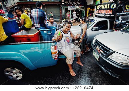 KO SAMUI, THAILAND - APRIL 13: Unidentified young thai man in the trunk of a pickup in a water fight festival or Songkran Festival (Thai New Year) on April 13, 2014 in Chaweng Main Road, Ko Samui island, Thailand.