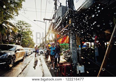 KO SAMUI, THAILAND - APRIL 13: Unidentified people shower water at the camera on Songkran Festival (Thai New Year) on April 13, 2014 in Chaweng Main Road, Ko Samui island, Thailand.