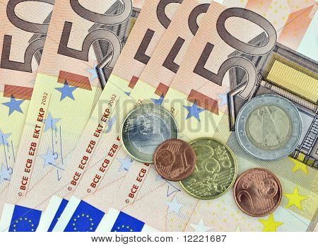 Closeup of fifty euro banknotes with coins