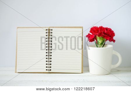 Empty notepad and red Carnation flower in a cup on the white wooden table.