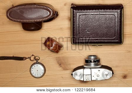 old photograph equipment on wooden table with camera and tools