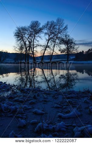 Blue sky and the outlines of trees on a frosty winter river