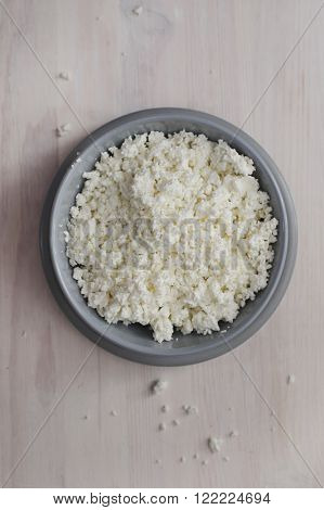 Cottage cheese granulated in grey bowl. Natural lighting, view from top.