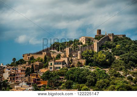 Capdepera castle on green hill in Mallorca island, Spain. Beautiful landsacape with medieval architecture, green trees and blue sky with clouds on a sunny day.