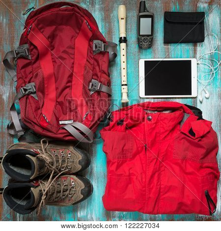 Flat lay photo of equipment for adventure. Red clothes and equipment for travel on the old wooden background. Top view.