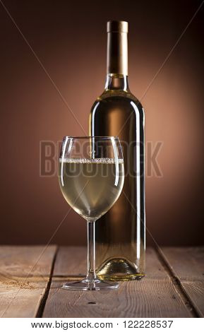 Wineglass and bottle with white wine on wooden background