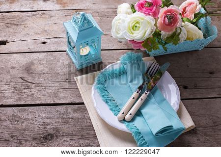 Table setting. Pink and white flowers candle in blue lantern knife and fork on white plate on vintage wooden background. Selective focus. Place for text.