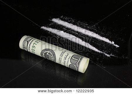 cocaine and one hundred dollars on a dark background