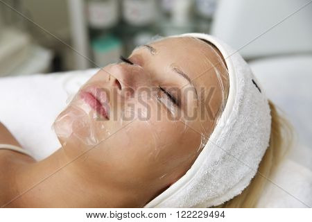 Beautiful young woman lying on massage table while natural facial mask is applied on her face.