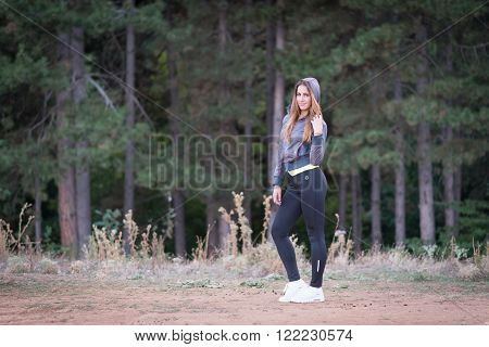 Picture of sexy yound fitness blonde model in nature posing before jogging