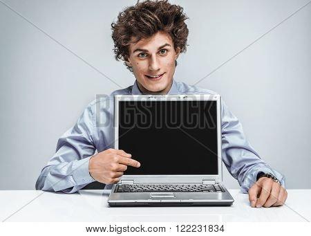 Smiling businessman at the workplace looking at camera and showing at screen laptop. Business concept