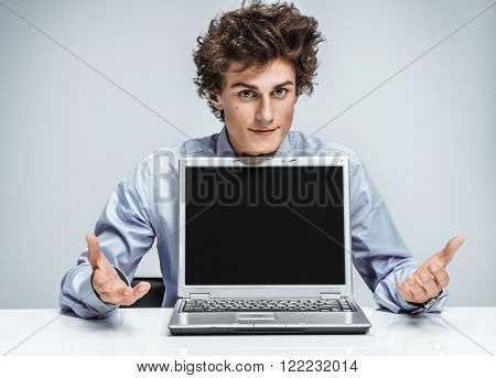 Friendly young manager is glad to see the client. Smiling businessman at the workplace looking at camera on gray background. Business concept