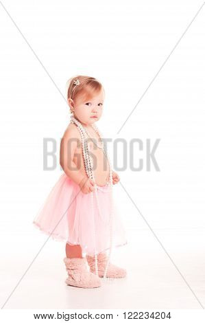 Smiling baby girl 1-2 year old standing over white. Wearing stylish skirt and pearl necklace. Looking at camera. Childhood.