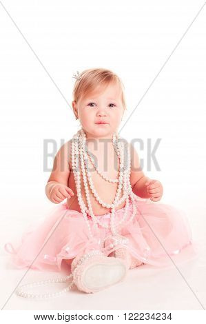 Cute baby girl 1-2 year old playing with mother's necklace over white. Looking at camera. Childhood.