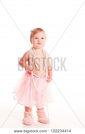 Cute baby girl 1-2 year old wearing mother's necklace and fluffy skirt over white. Looking at camera. Childhood.