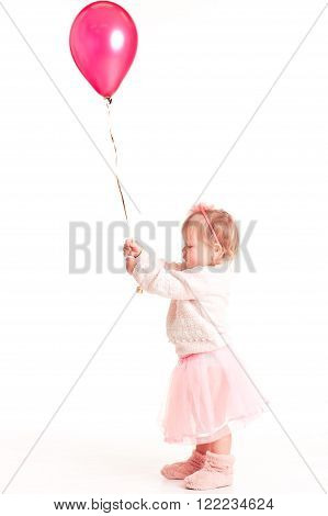 Cute kid girl 1-2 year old playing with pink balloon over white. Playful. Childhood.