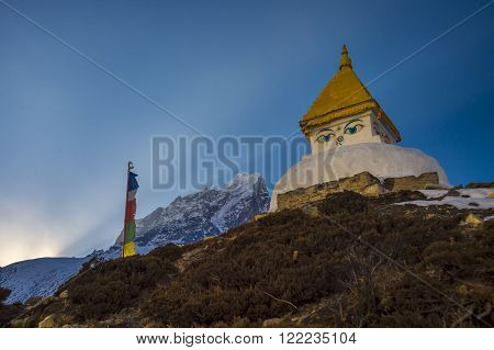Beautiful view of a stupa when sun disappears behind a moutain on the way to Everest base camp in Nepal