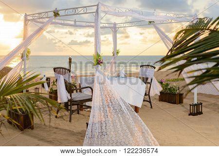 Romantic dinner setting on the beach at sunset.