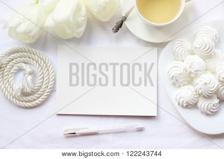 Mockup for presentations with white tulips and green tea. Desktop workplace designer artist painter top view. Modern trend template for advertising. Product mockup wedding mockup
