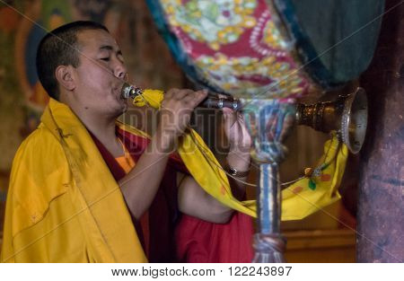 Leh, India - AUGUST 23, 2007: Buddhist monk playing on shell during buddhist ceremony at Thiksay Monastery.