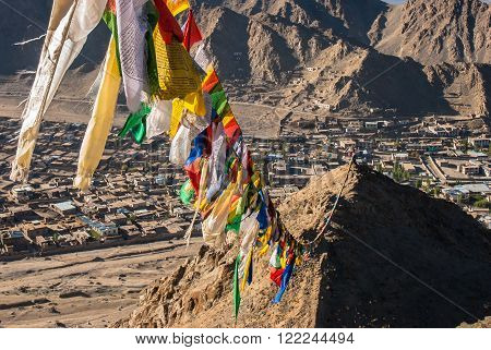 Prayer flags with traditional wooden print on them. They are used to bless the surrounding countryside and for other purposes. Here, prayer flags connect the two over Leh, Ladakh, India.