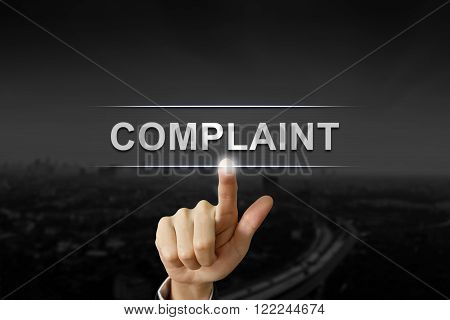 business hand clicking complaint button on black blurred background